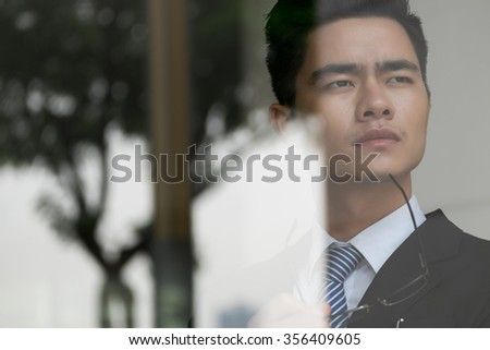 Face of pensive Asian businessman pondering over new idea
