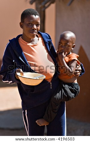 Face of poverty in the third world, mother with child in the harsh sun of Kalahari desert, social issues series - stock photo