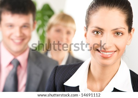 Face of pretty smiling woman on background of her business partners - stock photo