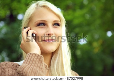 Face of radiant young blonde woman with an amused expression on her mobile phone against green foliage. - stock photo