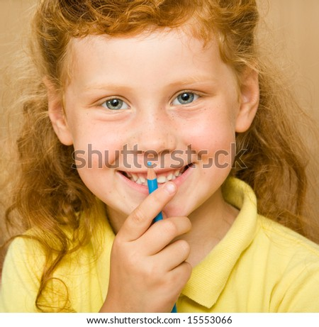 Face of red-headed girl holding blue pencil by her mouth looking at camera with smile - stock photo