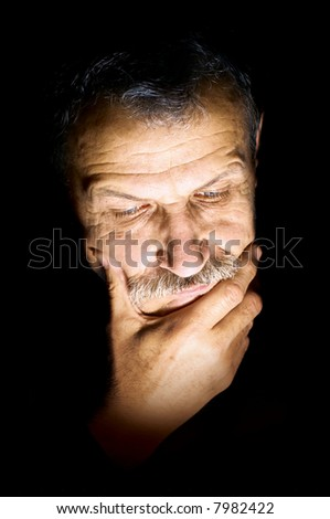 Face of sad middle aged man isolated on black
