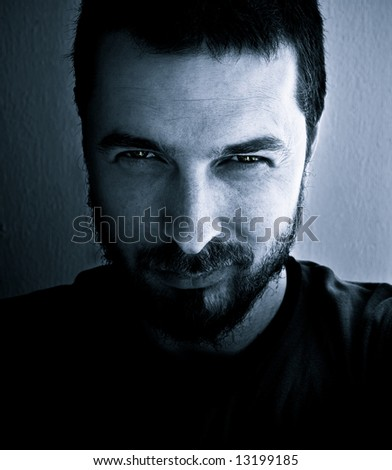Face of scary man with evil smile - stock photo