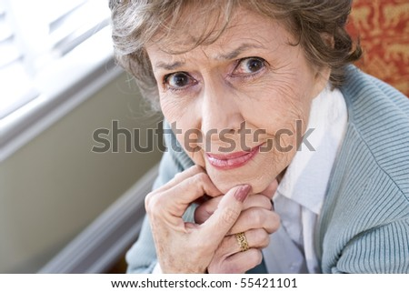 Face of serious elderly woman in 70s staring at camera