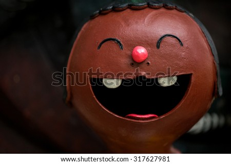 face of smile doll on dark brown background