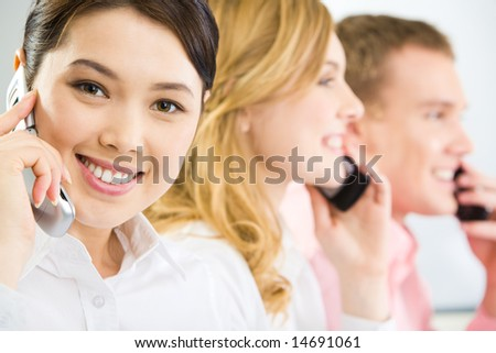 Face of smiling businesswoman making phone call and looking at camera with smile on background of two phoning people - stock photo