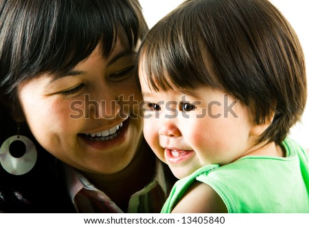 Face of smiling little girl with her loving mother at the background - stock photo