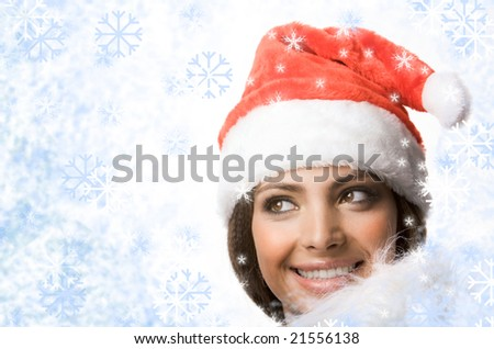Face of smiling woman in Santa cap looking out of snowflakes