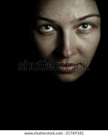 Face of spooky mystery woman in the dark - stock photo