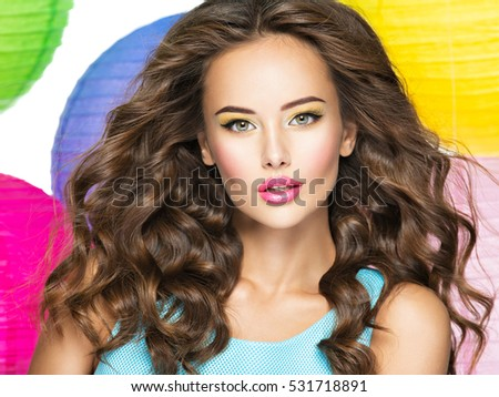 Face of the beautiful sensual woman with long curly hair. Pretty young girl with fashion make-up.