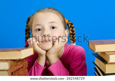 face of the schoolgirl of 9 years. On the right and at the left piles of books. A photo on a blue background - stock photo