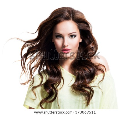 Face of the sensuality beautiful woman with long brown curly hair in yellow shirt