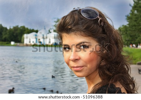 face of the woman with sunglasses near the pond - stock photo