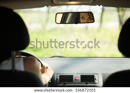 Face of women driving the car which is visible in mirror. - stock photo