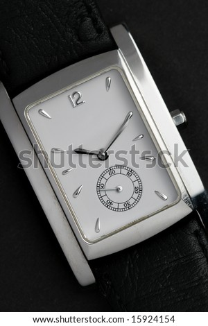 Face of wristwatch close-up over black background - stock photo
