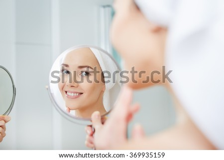 face of young beautiful healthy woman and reflection in the mirror - stock photo