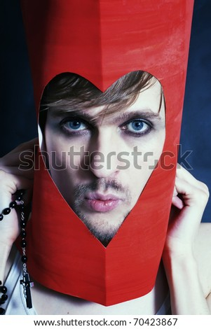 Face of young man peering from hole in heart-shaped - stock photo