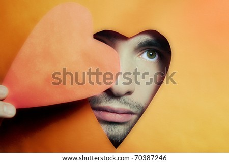 Face of young man peering from hole in heart-shaped closeup - stock photo