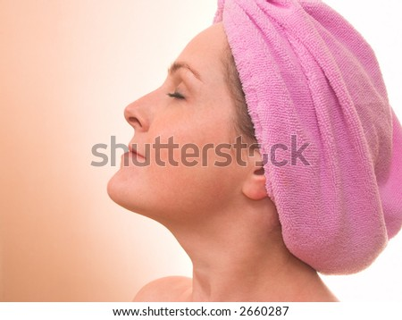 Face of young woman in a hair towel with closed eyes as in spa took half face over peachy background with copyspace - stock photo