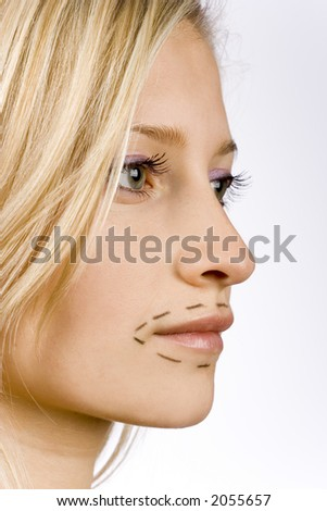 face of young woman prepared to plastic surgery (grey background) - stock photo