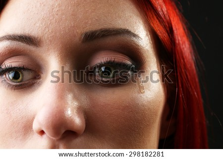 Face of young woman with tear drop close up - stock photo