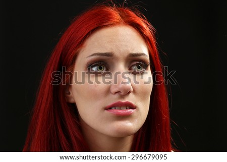 Face of young woman with tear drop on dark background - stock photo