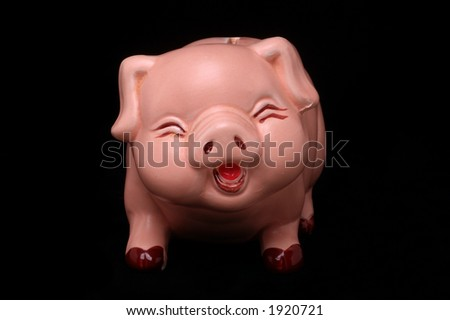 Face on view of pink piggy bank on black background - stock photo