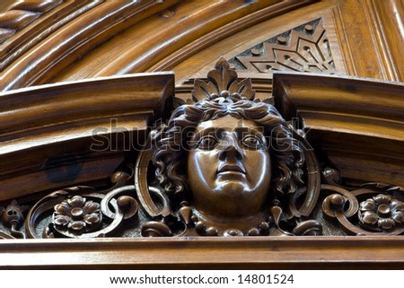 Face ornament on old wood door in Spain - stock photo