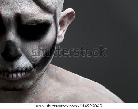 face painted with a skull. The photo shows a young man with his face painted with a skull  and with the intention of conveying horror or mystery. - stock photo