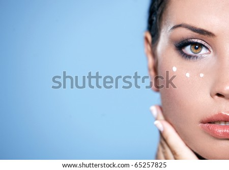 Face part of beautiful woman with cream on face on natural background