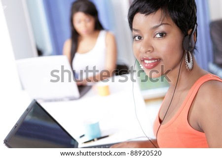 Face portrait of a pretty office girl in busy office looking up with smile - stock photo