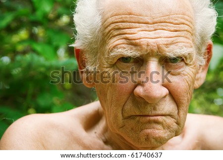 face portrait of an old angry frowning senior man - stock photo