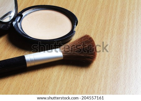 Face powder and brush on the wooden floor. - stock photo