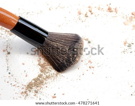 Face powder and brush on white background
