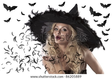 face shot of a cute and sexy girl dressed with a huge witch hat with feathers blowing a kiss - stock photo
