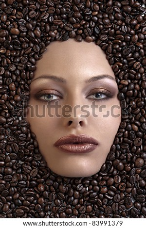 face shot of a pretty girl immersed in coffee beans - stock photo