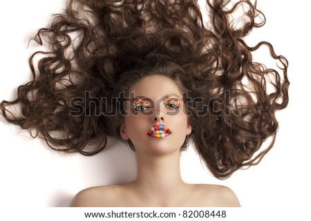 face shot of a pretty girl laying on white with a colourful make up