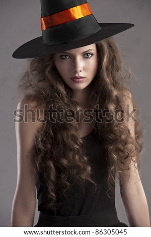 face shot of a young and beautiful girl dressed up for halloween with a huge black witch hat looking straight into the cam - stock photo