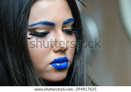Face shot of woman with blue lipstick and unique makeup, covered hair with a white hood
