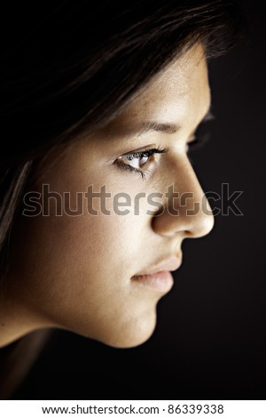 Face side view of a cute pretty teenage female girl isolated against a black background - stock photo