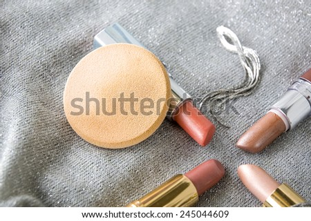 face sponge powder and pink lipstick on silver background - stock photo