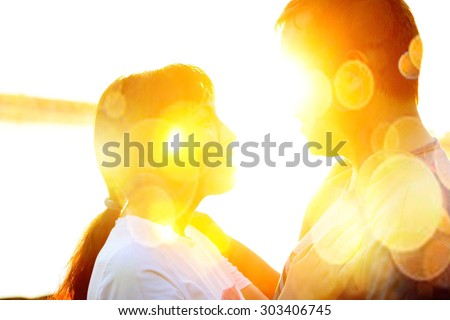 Face to face. Young couple in love silhouette hugging and looking at each other outdoors at night neon city or sun light bokeh background Woman and man outdoor on nature backdrop. Nice Sunset