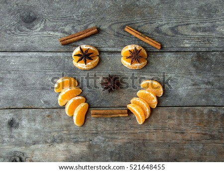 face with mandarin, anise and cinnamon on wooden background