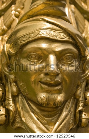 Face with the gold mask in the garden of Versailles, France