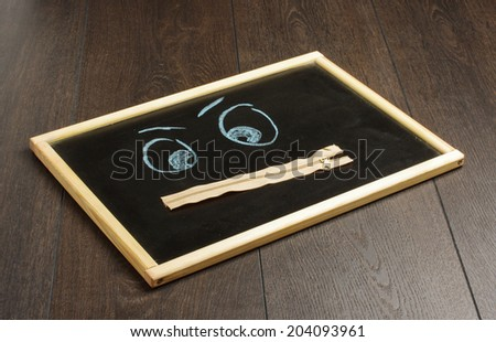 Face with zip mouth on the blackboard - stock photo