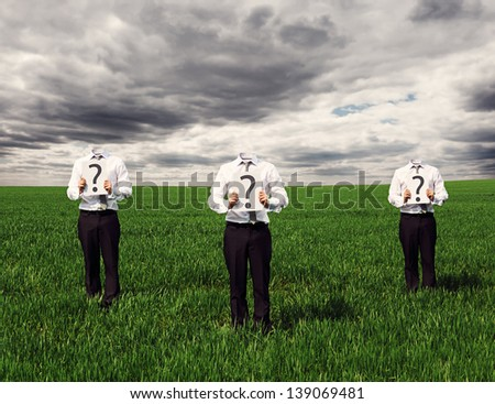 faceless businessmen standing on the green grass and holding placard with question mark - stock photo