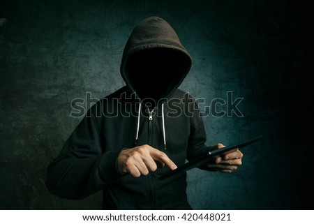 Faceless hooded unidentifiable male person using tablet computer, internet hacker and online security concept. - stock photo