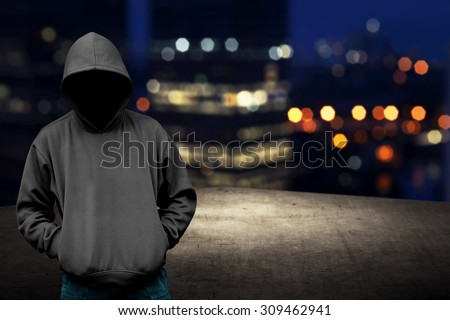 Faceless man in hood on the rooftop with city background at night time - stock photo
