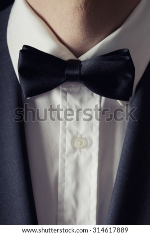 Faceless man with black bowtie, white shirt and charcoal suit jacket on.