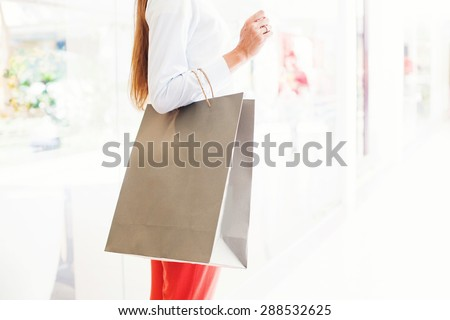 faceless photograph of woman holding a blank paper shopping back (mock up to paste a logo) - stock photo